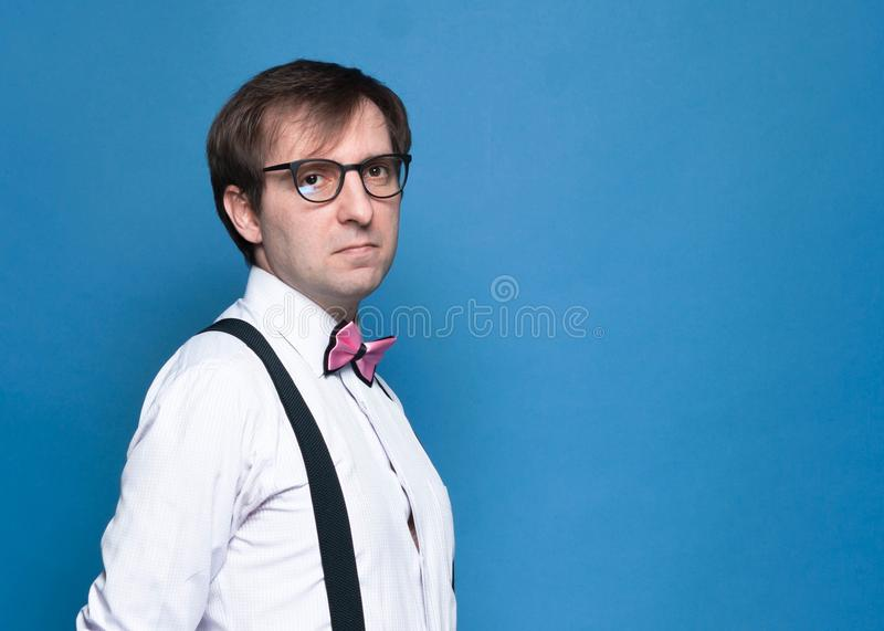 handsome man in pink shirt, bow tie, black suspender and glasses looking at camera stock photography