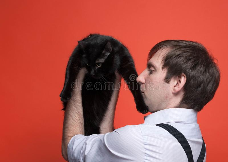 Handsome man in pink shirt with rolled up sleeves holding on outstretched arms cute black cat and kissing it paw. Side view of handsome man in pink shirt with royalty free stock photo