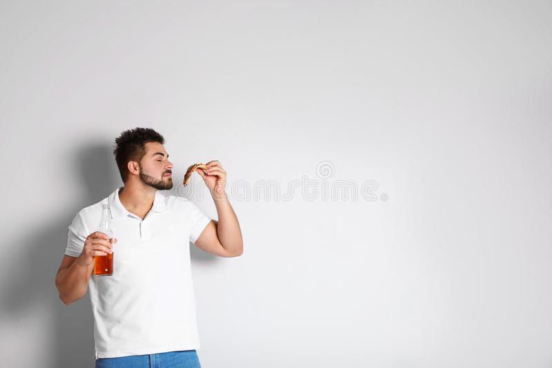 Handsome man with pizza and beer on background, space for text royalty free stock photography