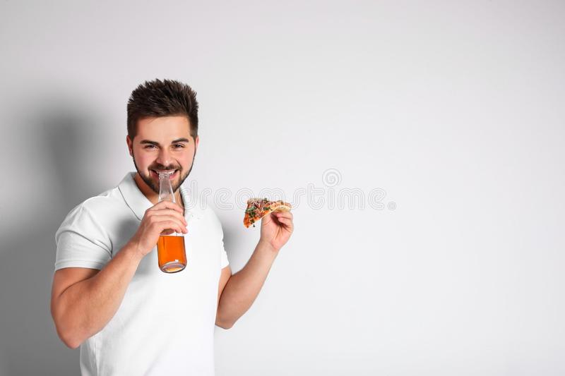 Handsome man with pizza and beer on background, space for text stock image