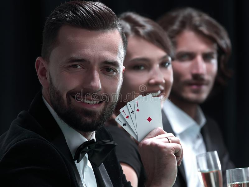 Handsome man playing in casino. Elegant young smiling people are drinking wine at the poker table royalty free stock photo