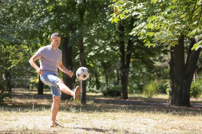 Handsome man playing football outdoors stock photos
