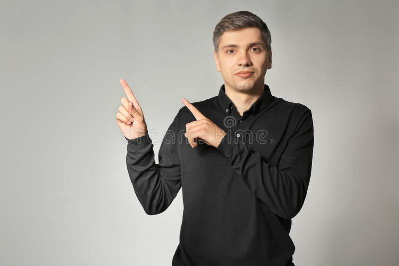 Handsome man pointing at something on grey background stock images