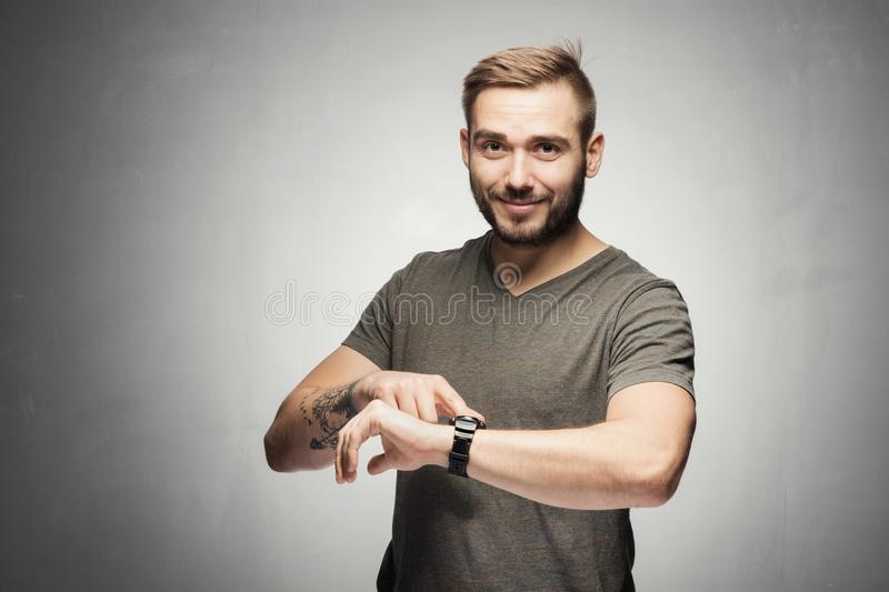 Handsome man pointing at a watch on the wrist royalty free stock photos