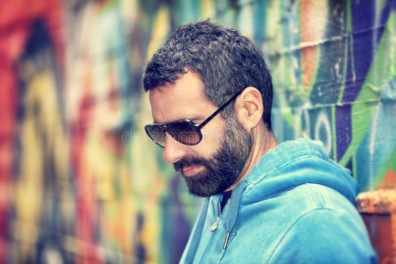 Handsome man portrait. Closeup portrait of handsome man with stylish beard and sunglasses, standing over colorful city wall background, fashion street look royalty free stock photo