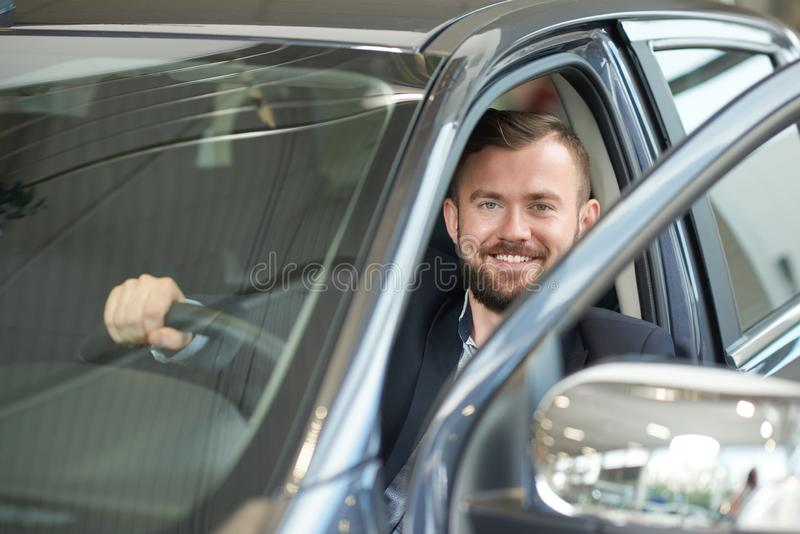 Handsome man posing in car. stock photography