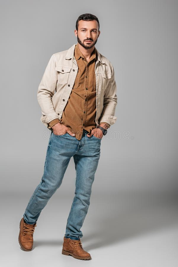 Handsome man posing in corduroy shirt and autumn jacket with hands in pockets of jeans. On grey royalty free stock photo
