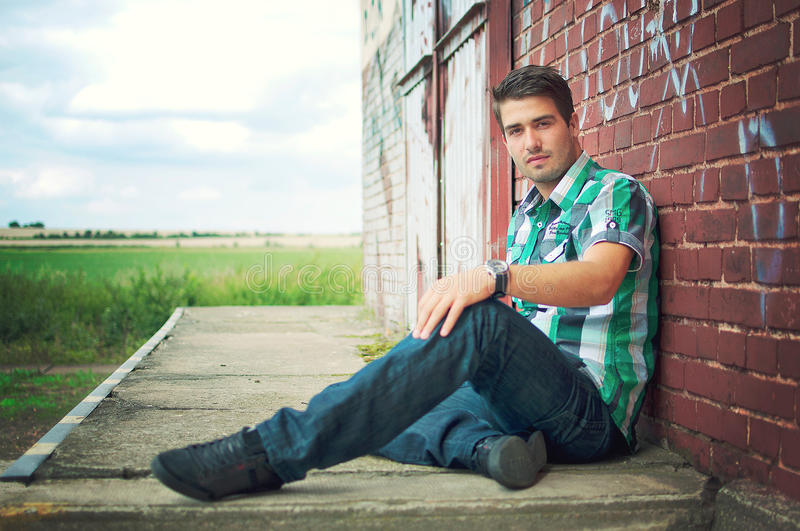 Handsome man posing outdoor over graffiti wall stock image
