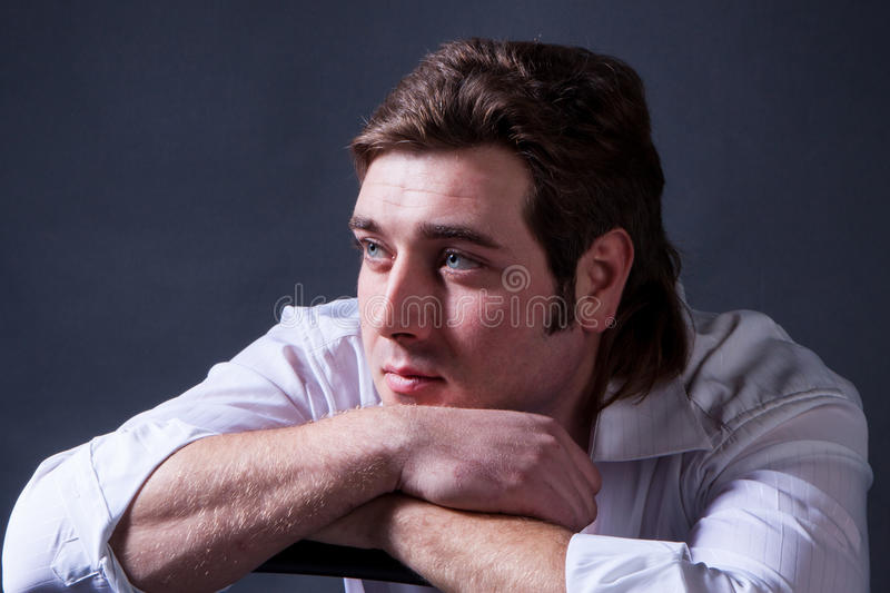 Handsome man. Posing in white shirt on dark background in studio stock photography
