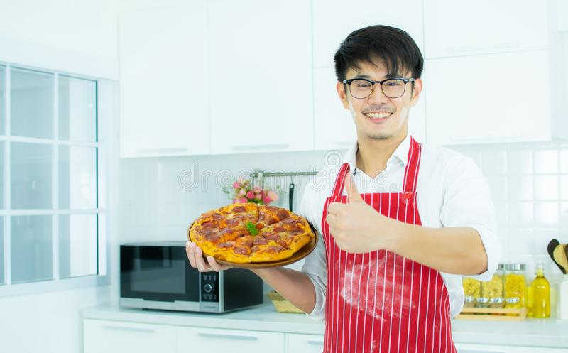 A man is preparing a pizza. A handsome man is preparing pizza in the kitchen royalty free stock photo