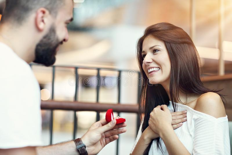 Handsome man proposing to beautiful woman in cafe. Picture of handsome men proposing to beautiful women in cafe stock image