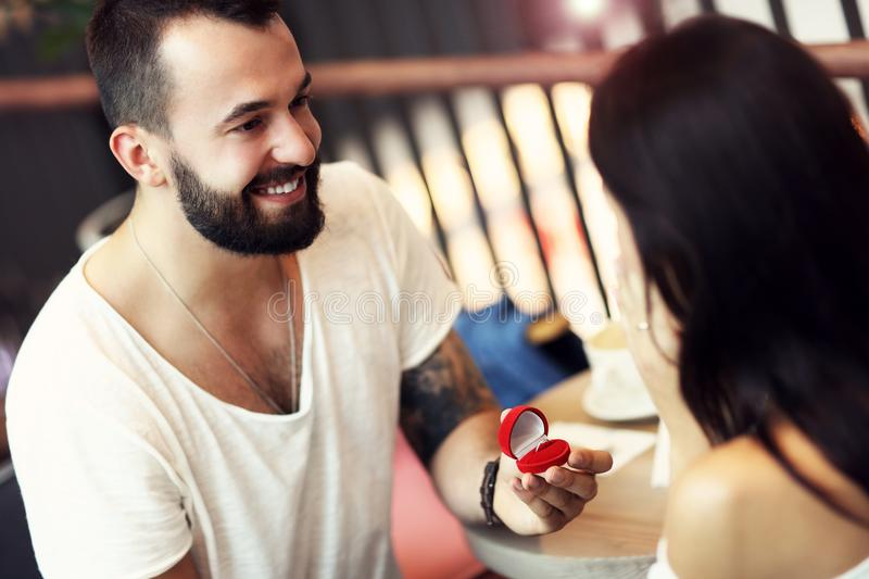 Handsome man proposing to beautiful woman in cafe. Picture of handsome men proposing to beautiful women in cafe royalty free stock image