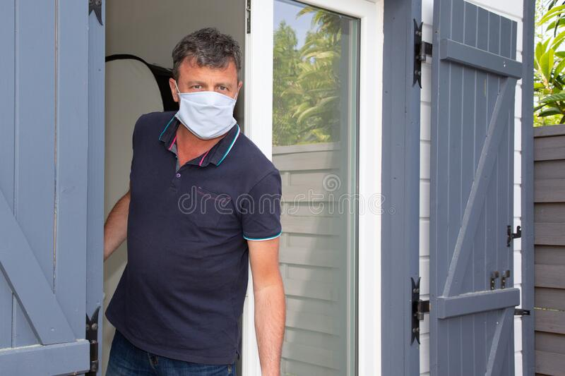 Handsome man with protective mask confined in quarantine to prevent coronavirus covid-19 spread to home door. An handsome man with protective mask confined in royalty free stock photo