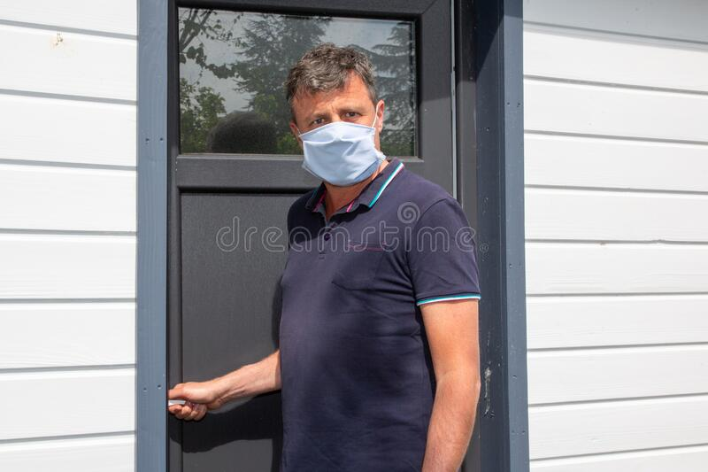 Handsome man with protective mask front home door confined in quarantine during epidemic coronavirus covid-19. A handsome man with protective mask front home royalty free stock photo