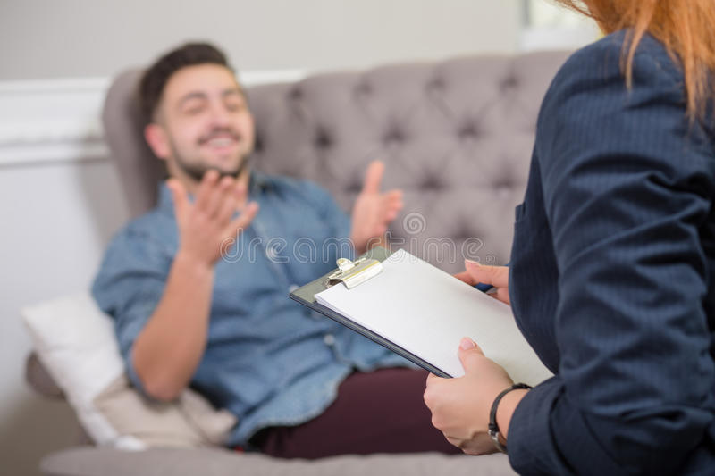 Handsome man at the psychotherapist. Close-up portrait of female psychiatrist making notes in front of patient during psychological therapy session stock photography