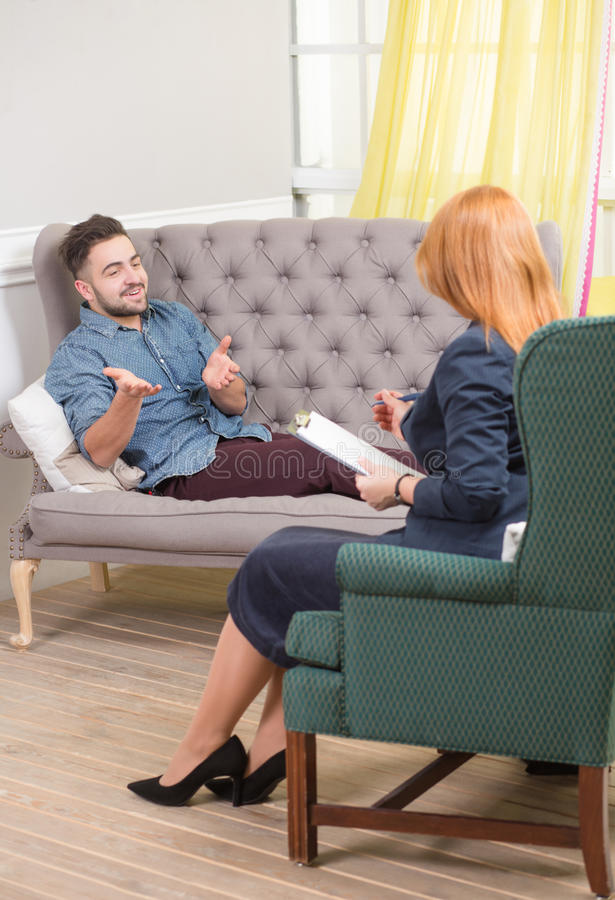 Handsome man at the psychotherapist. Portrait of gesticulating men talking with psychologist. Handsome men reclining comfortably on a couch talking to his stock image