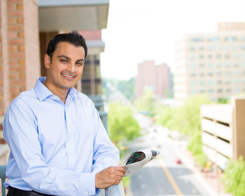 Handsome man reading on balcony stock images