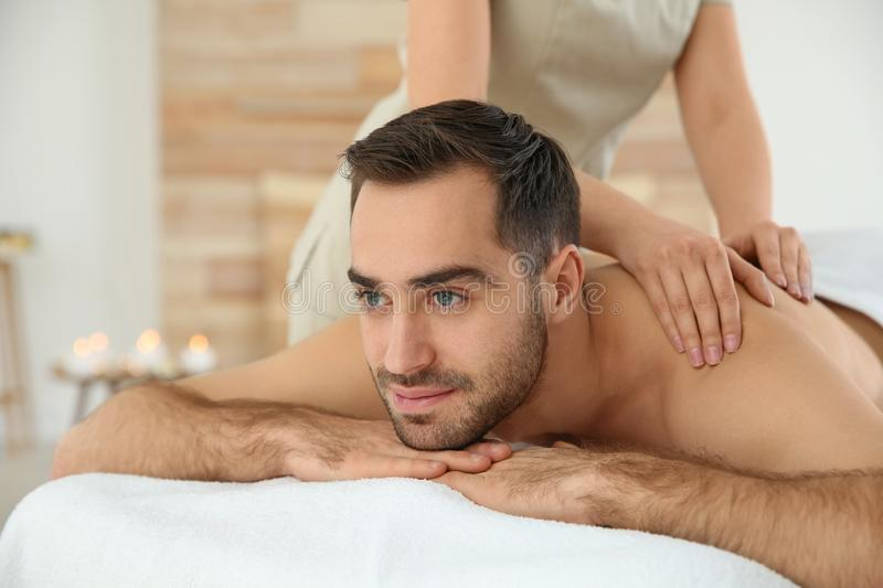 Handsome man receiving back massage. In spa salon stock photo