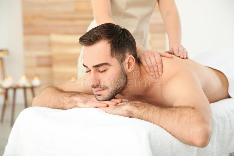Handsome man receiving back massage. In spa salon stock photos