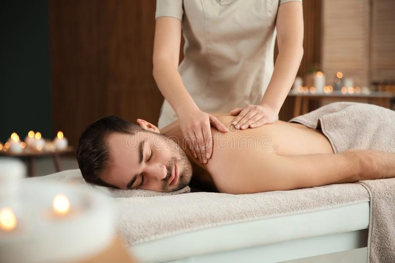 Handsome man receiving back massage. In spa salon royalty free stock image