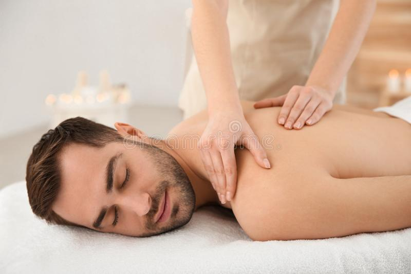 Handsome man receiving back massage. In spa salon stock image