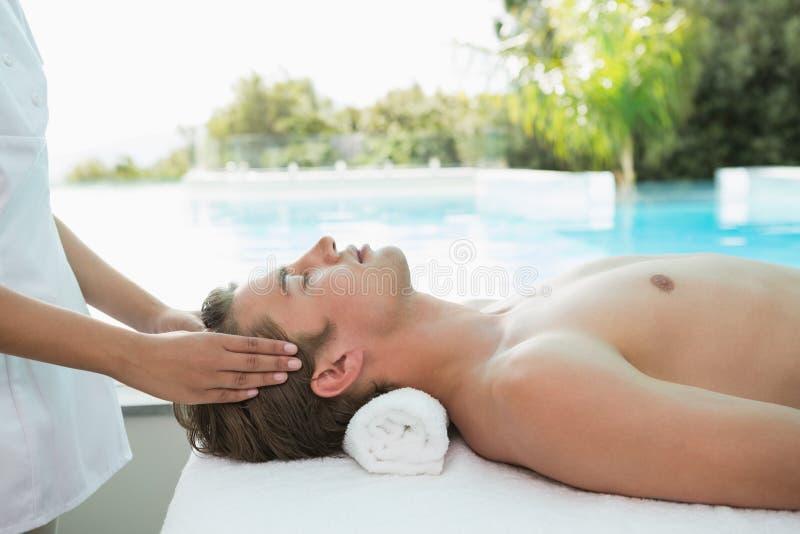 Handsome man receiving head massage at spa center. Side view of a handsome young man receiving head massage at spa center stock images