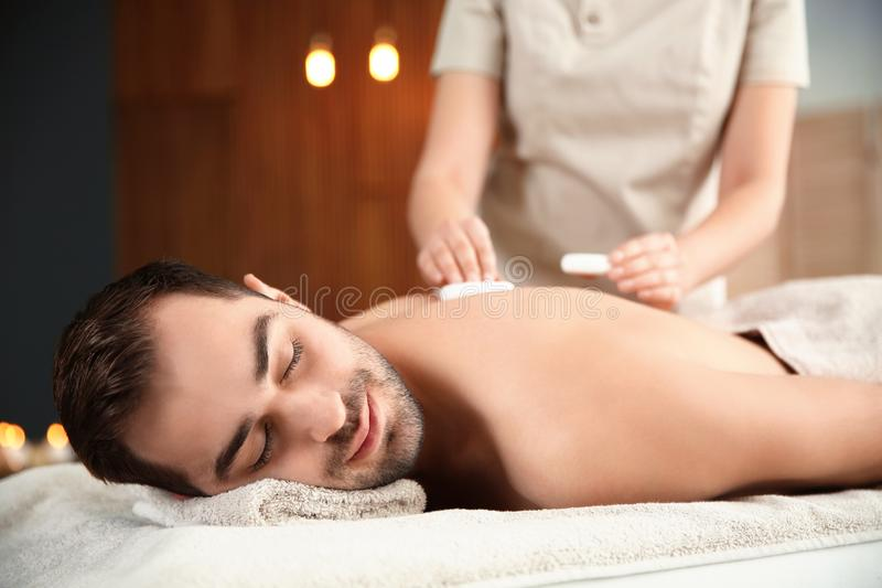 Handsome man receiving hot stone massage. In spa salon stock photography