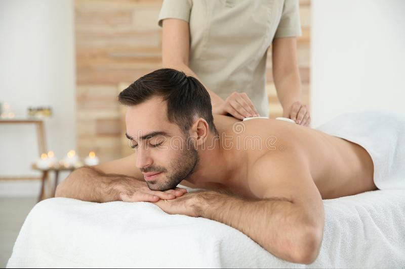 Handsome man receiving hot stone massage. In spa salon royalty free stock images