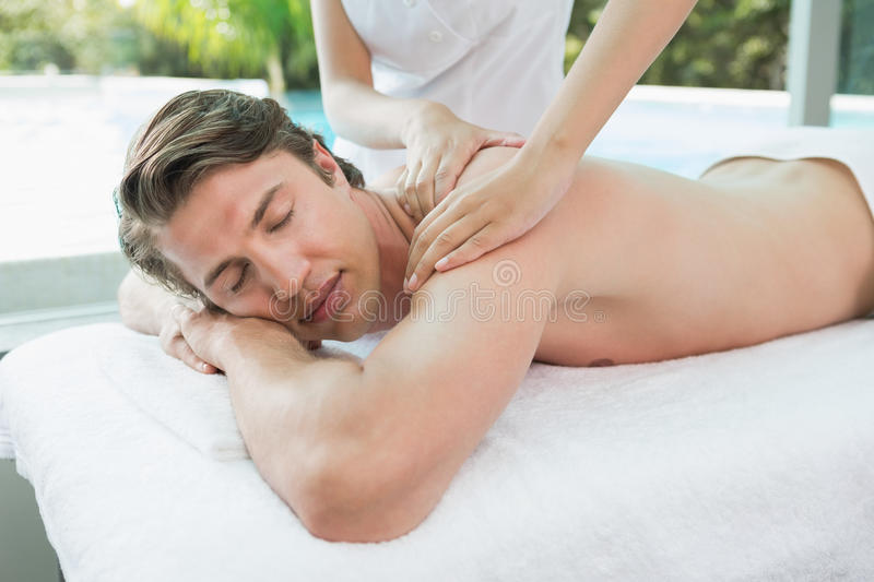 Handsome man receiving shoulder massage at spa center. Side view of a handsome young man receiving shoulder massage at spa center royalty free stock photography