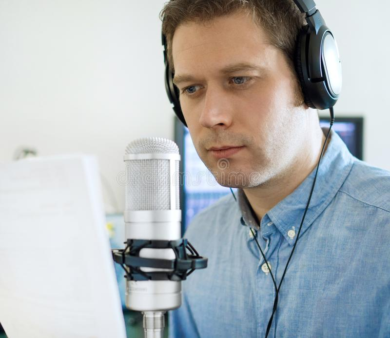Handsome man recording an advertisement. stock image
