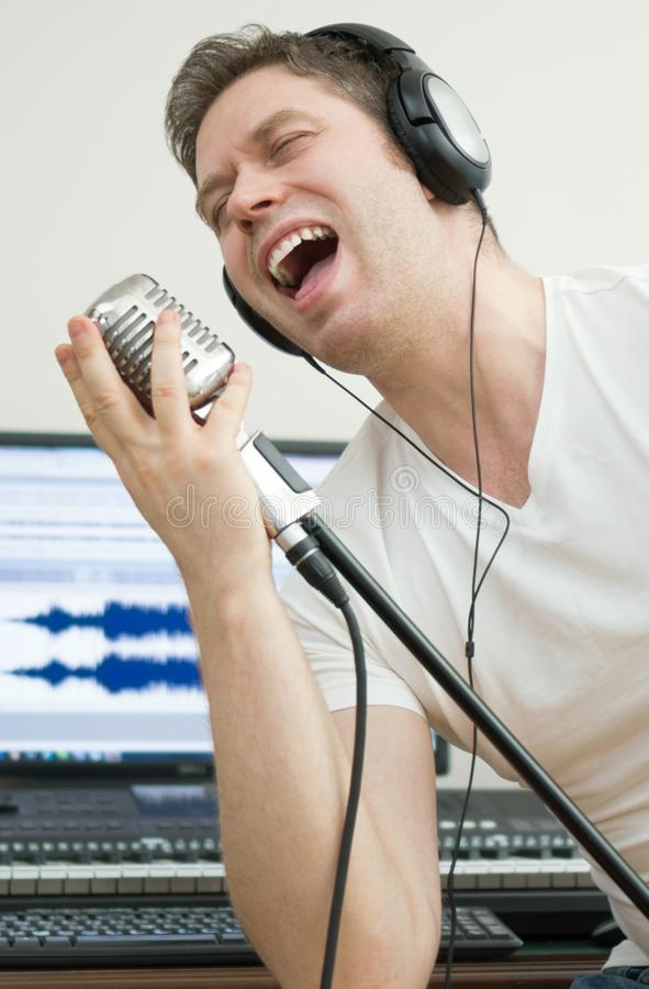Handsome man recording a song. royalty free stock image