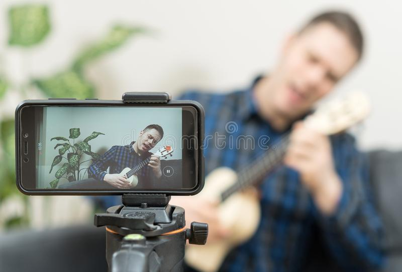 Handsome man recording song. Vlogging concept royalty free stock images