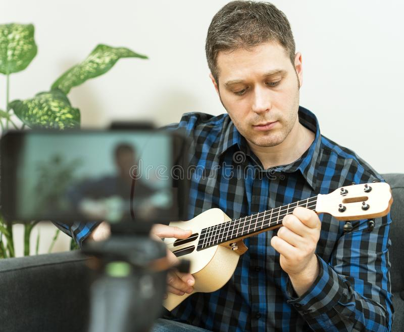 Handsome man recording song. Vlogging concept stock photography
