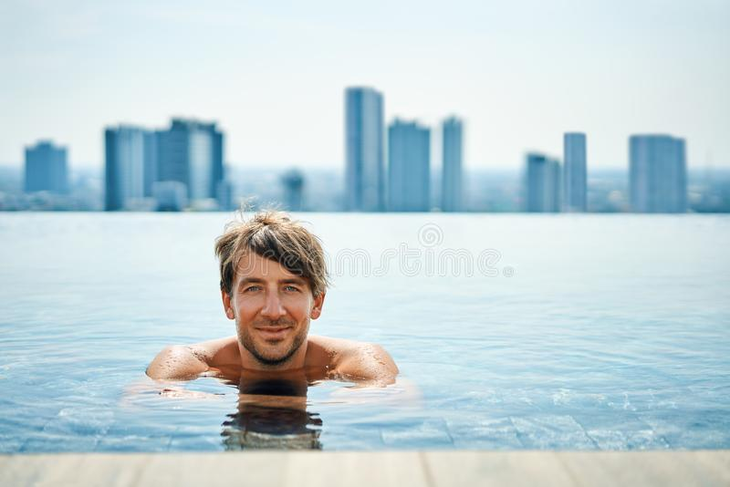 Handsome man relax in swimming pool. Summer vacation concept stock image