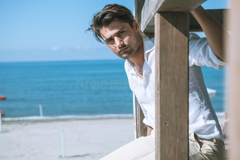 Handsome man relaxed at the sea, overlooking a wooden structure. Sea and blue sky. stock photography