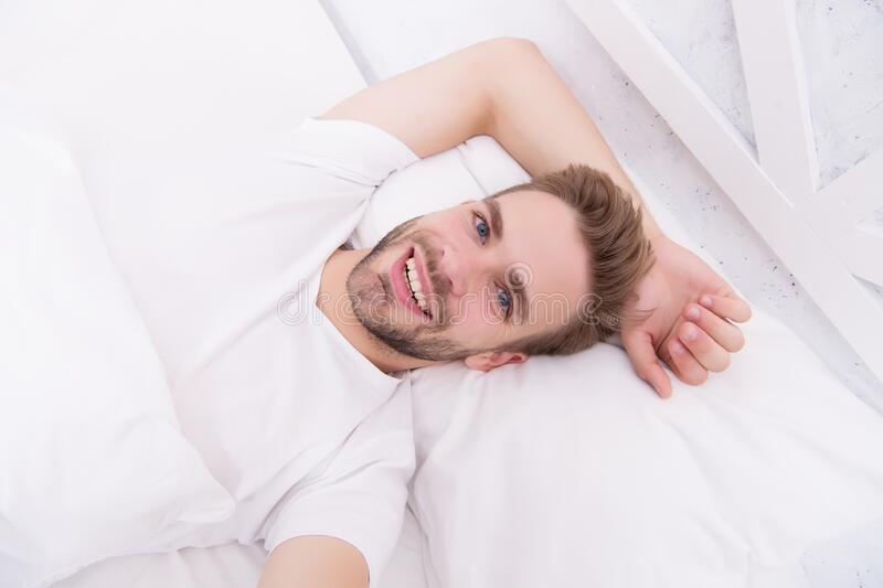 Handsome man relaxing in bed. Establish regular nightly sleep pattern. Practice calming activities such as meditation. Before going to bed. Healthy sleep royalty free stock image