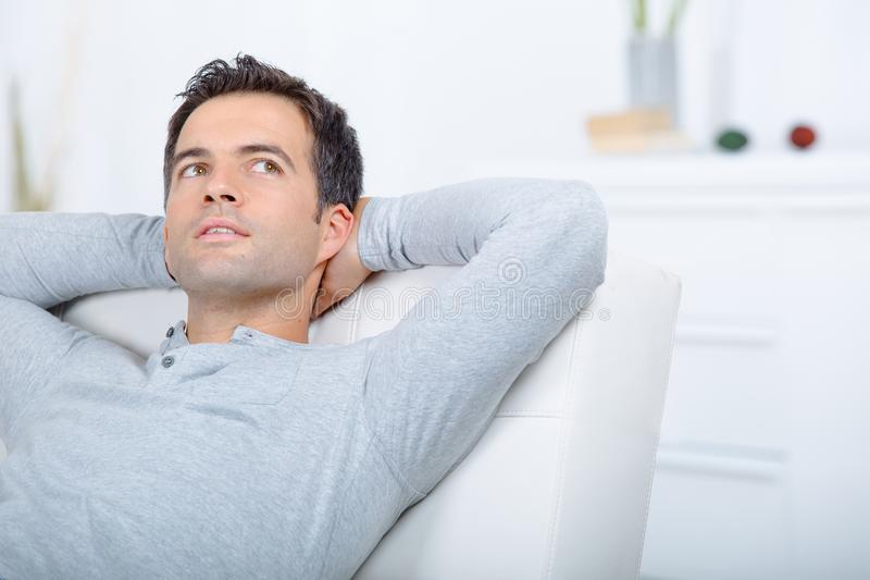 Handsome man relaxing at home stock photos