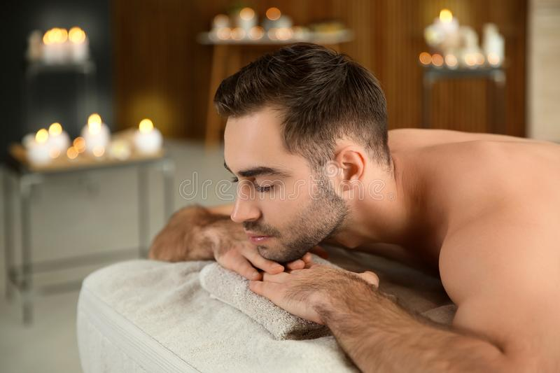 Handsome man relaxing on massage table. In spa salon stock images