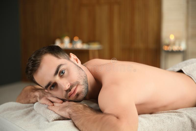 Handsome man relaxing on massage table. In spa salon stock photography