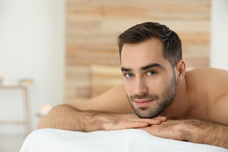 Handsome man relaxing on massage table in spa salon. Space for text stock photo