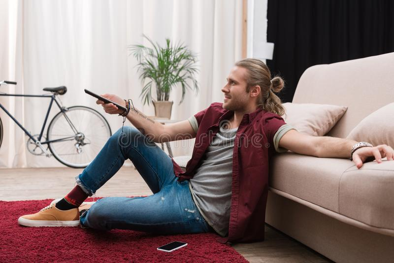 Handsome man with remote control watching tv. At home royalty free stock photos
