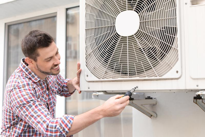 Handsome man repairing air conditioner. Outdoors stock images