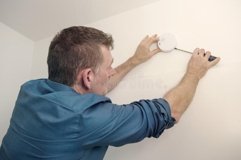 Handsome man repairing a smoke detector royalty free stock photos