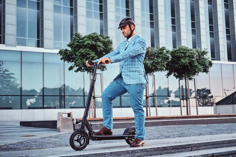 Handsome man is riding his scooter near offices building stock images