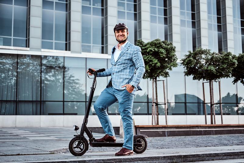 Handsome man is riding his scooter near offices building royalty free stock photo