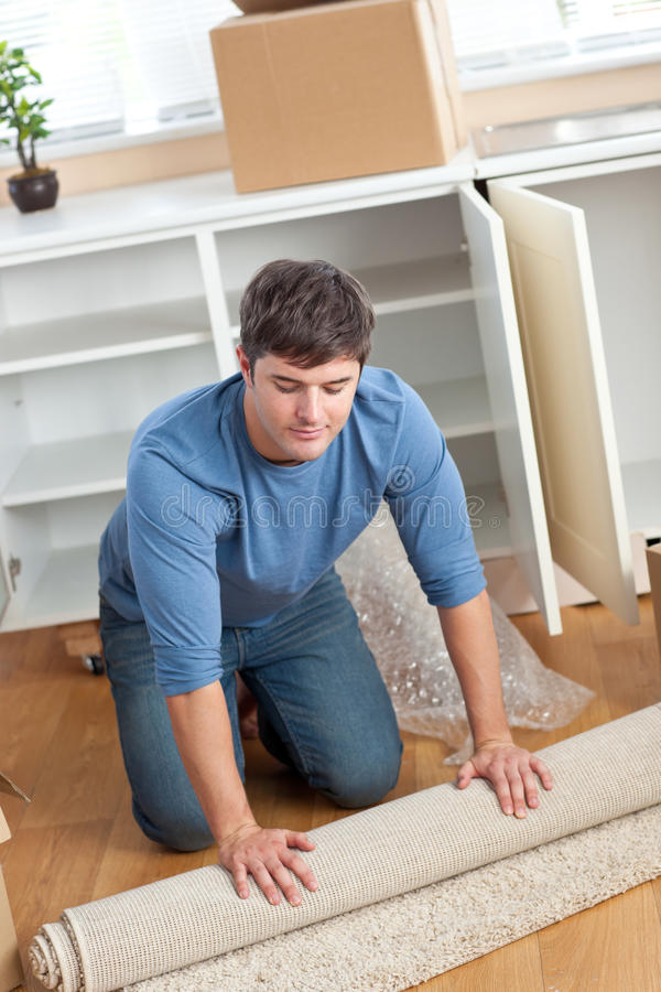 Download Handsome Man Rolling A Carpet Out Stock Photo - Image: 16262602
