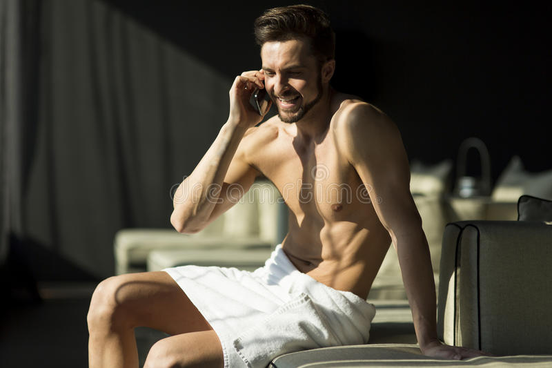 Handsome man in the room. Man wrapped in a towel sitting in a room and holding a phone stock photo