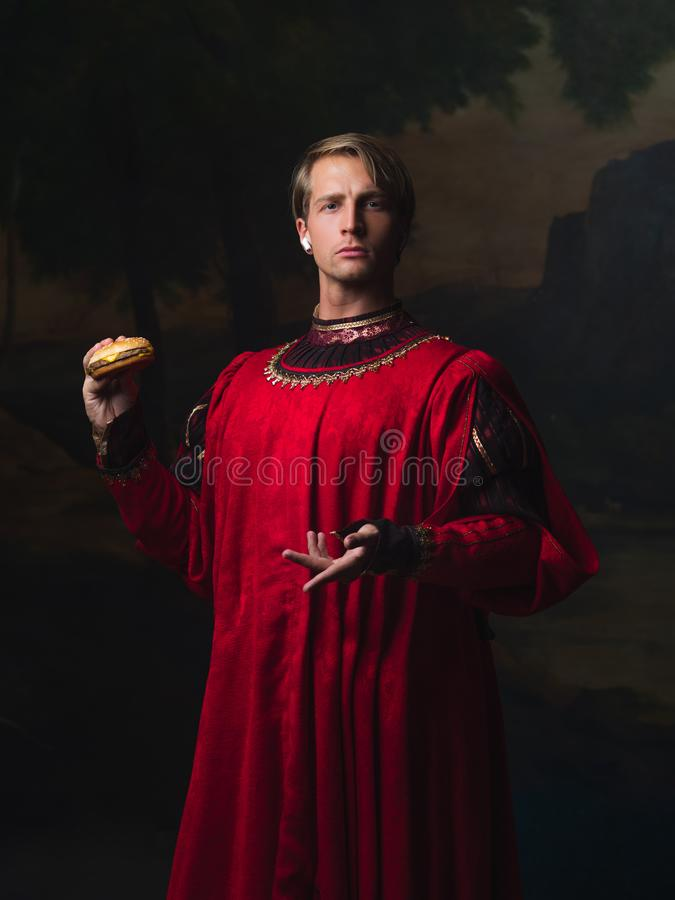 Handsome man in a Royal red doublet eating fast food. stock image