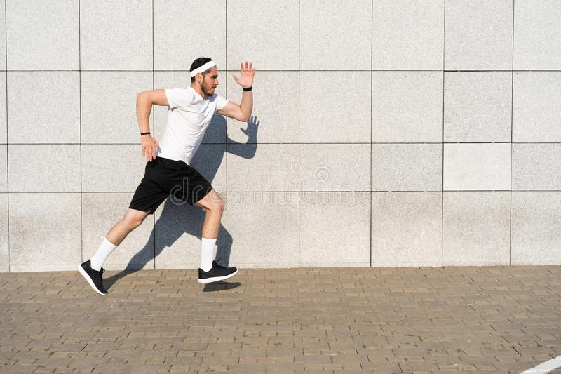 Handsome man running in the city. Fitness, workout, sport, lifestyle concept. Handsome man running in the city. Fitness, workout, sport, lifestyle concept royalty free stock photography