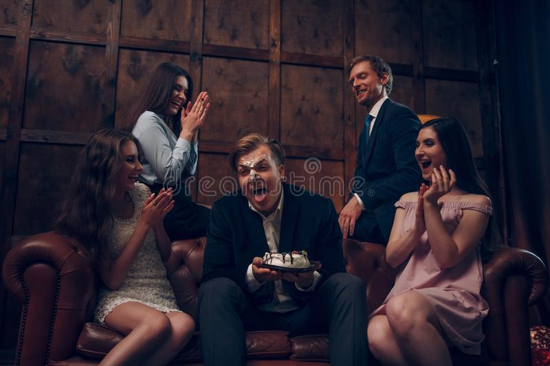 Handsome man`s face covered in birthday cake royalty free stock photo